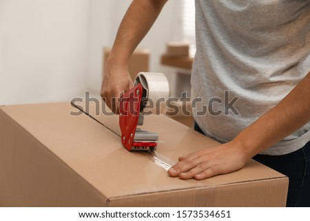 Woman packing cardboard box indoors, closeup. Moving day Royalty-Free Stock Photo #1573534651