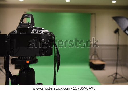 Professional photography studio showing behind the scenes lights, set up and green screen blurred in the background.