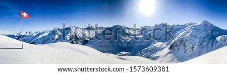 swiss alps mountain panorama in winter snow with the swiss flag on a sunny day with blue sky in the ski area gstaad Royalty-Free Stock Photo #1573609381