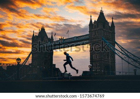 Running in London, Silhouette of runner who run near by Tower Bridge, London, United Kingdom. Concept photo for running competition in London as London marathon