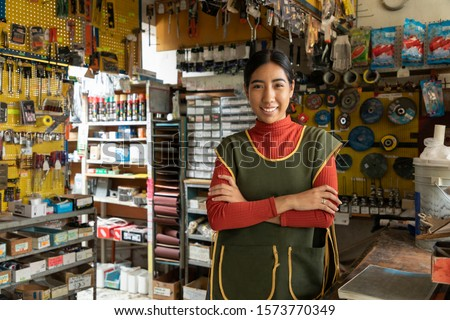 Smiling real worker attending a hardware store. interior detail Royalty-Free Stock Photo #1573770349