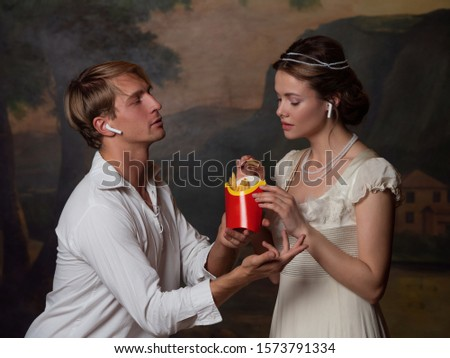 funny duet of medieval style and modern attributes, concept. Cute young couple in 18th and 19th century style, listening to modern music and eating fast food