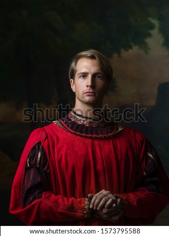 handsome man in a Royal red doublet. Young man, portrait in Renaissance style paintings Royalty-Free Stock Photo #1573795588