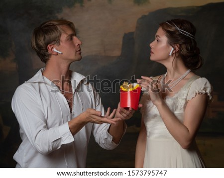 parody of the old, concept. Cute young couple in 18th and 19th century style, listening to modern music and eating fast food