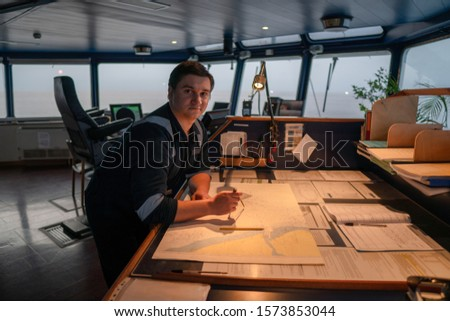 Marine navigational officer during navigational watch on Bridge . He does chart correction of nautical maps and publications. Work at sea #1573853044
