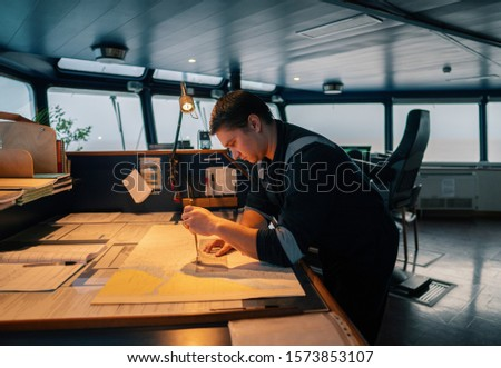 Marine navigational officer during navigational watch on Bridge . He does chart correction of nautical maps and publications. Work at sea #1573853107