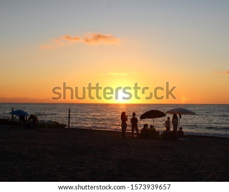 evocative image of sunset over the sea with promontory in the background and silhouette of people and umbrellas on the beach