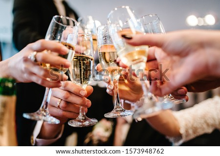 Cheers! People celebrate and raise glasses of wine for toast. Group of man and woman cheering with champagne. #1573948762