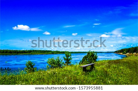 Summer green river shore bench. River shore bench view. Bench at river shore. Wooden bench on summer river shore #1573955881