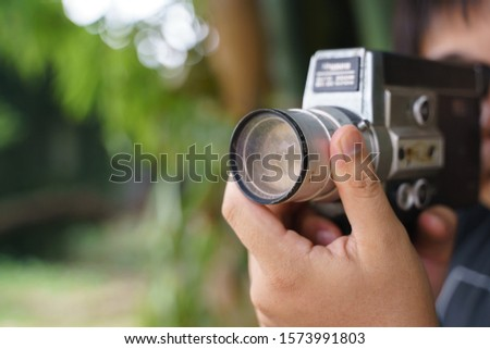 Hand holding old 8mm film video handheld recorder with defective lens #1573991803