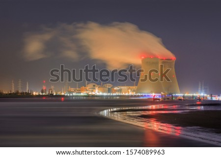 Night scene with view on riverbank with nuclear reactor Doel, Port of Antwerp, Belgium. Royalty-Free Stock Photo #1574089963