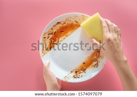 woman using yellow cleaning sponge to clean up and washing food stains and dirt on white dish after eating meal isolated on pink background. cleaning , healthcare and sanitation at home concept Royalty-Free Stock Photo #1574097079