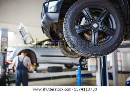 Car repair in the service station. Hands of a mechanic in overalls repairing the car on the lift without wheel, holding the tire and mechanical works. #1574110738