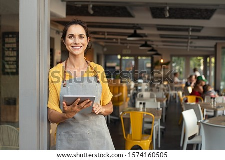 Portrait of happy woman standing at doorway of her store. Cheerful mature waitress waiting for clients at coffee shop. Successful small business owner in casual wearing grey apron standing at entrance Royalty-Free Stock Photo #1574160505