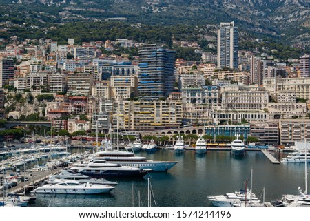 Marina of Monte Carlo In Monaco. Luxury yachts crowded into the Port Hercule, Monaco. Luxury buildings of the city in the background. #1574244496