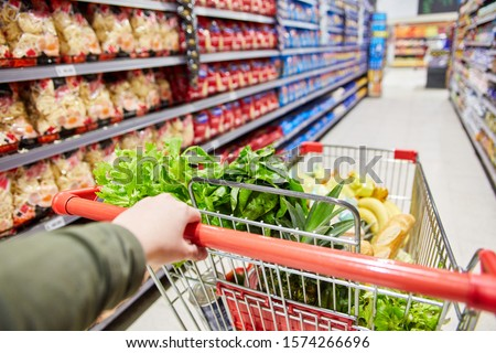 Customer pushes cart with food through a corridor in the supermarket Royalty-Free Stock Photo #1574266696