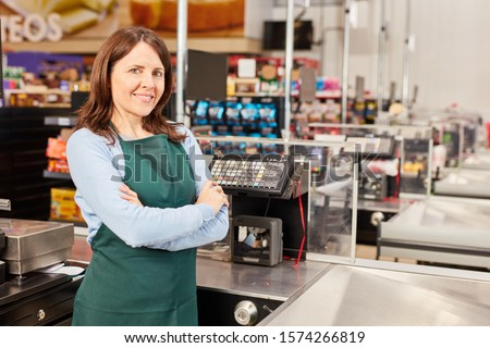 Woman in green apron as a cashier at the cash register in the supermarket or discounter #1574266819