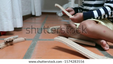 Child playing with traditional wooden car roads Toddler boy plays connecting road pieces together #1574283556