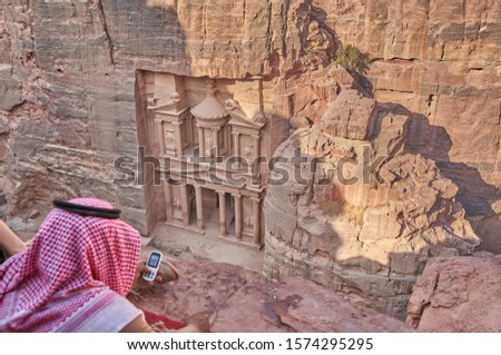 man in a traditional Jordan headscarf takes a picture of Pharaoh's treasury with a smartphone  - Petra, Jordan                      #1574295295
