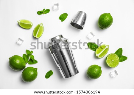 Flat lay composition with fresh juicy limes, mint, ice cubes and cocktail shaker on white background #1574306194