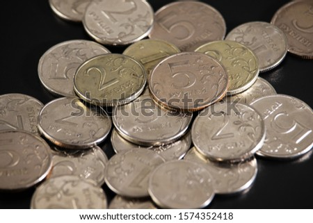 On a black background in a heap are small rubles coins. #1574352418