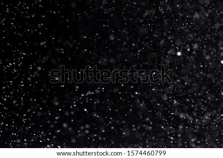 Falling  snow at night. Bokeh lights on black background, flying snowflakes in the air. Overlay texture. Snowstorm #1574460799
