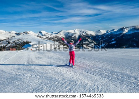Snowboarding girl going down the slope in Bad Kleinkirchheim, Austria. The slopes are perfectly groomed.There is a ski lift above the girl. Lots of snow caped mountains. Winter sports activity in Alps #1574465533