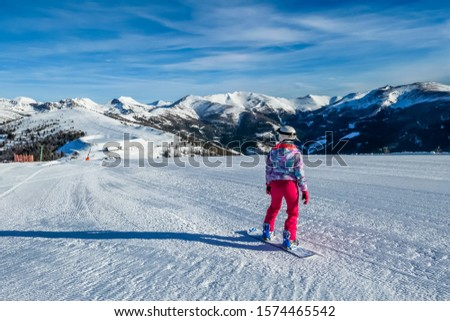 Snowboarding girl going down the slope in Bad Kleinkirchheim, Austria. The slopes are perfectly groomed.There is a ski lift above the girl. Lots of snow caped mountains. Winter sports activity in Alps #1574465542
