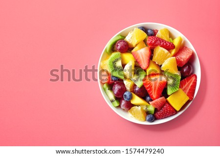Bowl of healthy fresh fruit salad on pink background, top view #1574479240