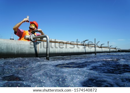 An engineer controlling a quality of water ,aerated activated sludge tank at a waste water treatment plant.  pollution                                  Royalty-Free Stock Photo #1574540872