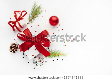 Christmas composition on a white background with white gift boxes, with a red ribbon with fir branches, toys, copy space for your congratulations #1574541556