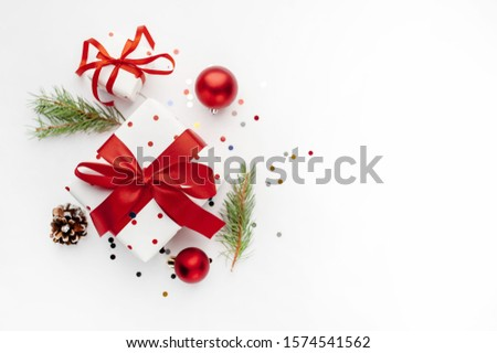 Christmas composition on a white background with white gift boxes, with a red ribbon with fir branches, toys, copy space for your congratulations #1574541562