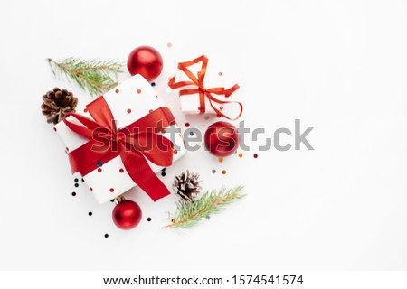 Christmas composition on a white background with white gift boxes, with a red ribbon with fir branches, toys, copy space for your congratulations #1574541574