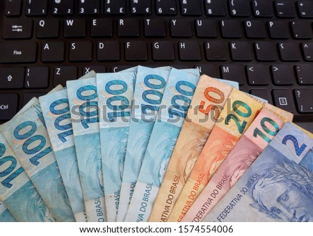 Brazilian Real banknotes on laptop keyboard. Brazilian money. Concept of digital business, office, finance and investment. #1574554006
