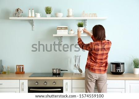 Woman putting houseplant on kitchen shelf #1574559100