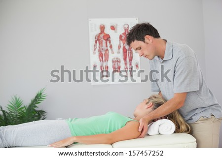 Attractive physiotherapist massaging patients neck in bright office #157457252