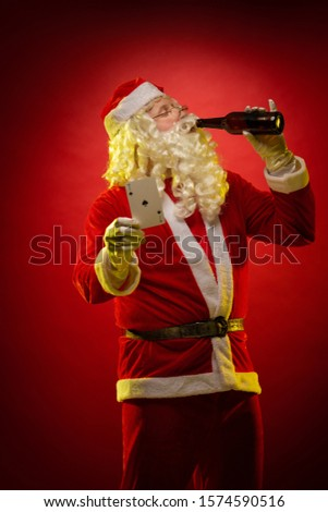 Male actor in a costume of Santa Claus holds playing cards and a bottle with alcohol in his hands, drinks and poses on a dark red background
