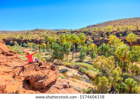 Carefree woman enjoying panorama above Finke River in dry season along Arankaia Walk. Aerial view of Palm Valley in Finke Gorge National Park, Northern Territory, Central Australia Outback. Royalty-Free Stock Photo #1574606158
