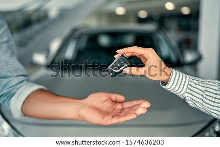 Close-up image a man buys a car and receives keys from the seller. Royalty-Free Stock Photo #1574636203