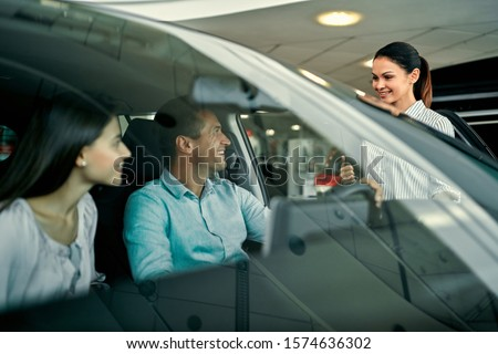 Young saleswoman shows a couple in love a car at a car dealership. Buying or renting a car. #1574636302