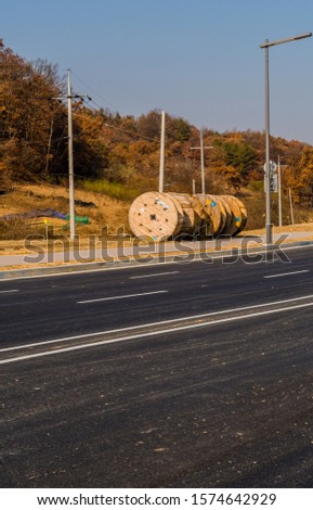 Large wooden industrial spools sitting on ground next to sidewalk of paved road. #1574642929
