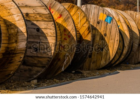 Large wooden industrial spools sitting on ground next to sidewalk of paved road. #1574642941