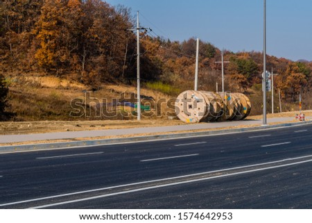 Large wooden industrial spools sitting on ground next to sidewalk of paved road. #1574642953