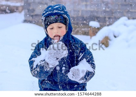 Little boy licks snow with gloves. child is eating snow. Sore throat after freezing. Outdoor games