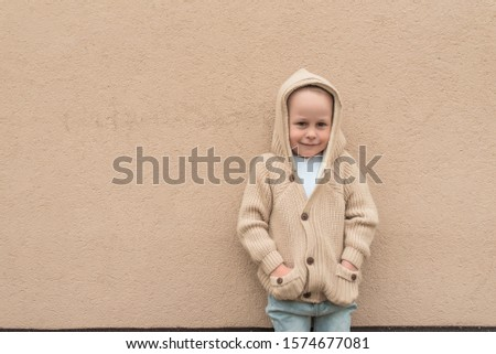 little boy 3-5 years old, stands in autumn beige wall, in warm casual clothes, sweater with hood, happy smiling, free space for copy text #1574677081