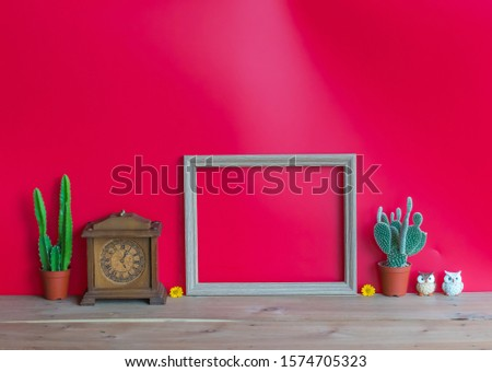 Beautiful  cactus,vintage    clock,blank  wooden  picture  frame  and  simulated  owl  on  wood  table  with  red  background,mockup