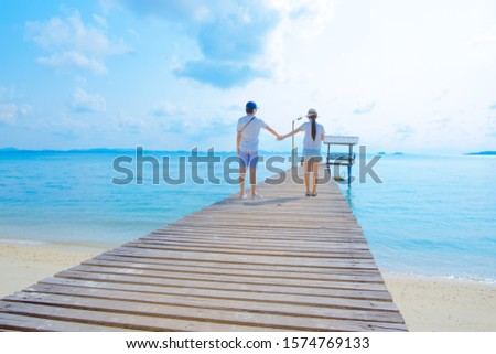 back view of couple on a wooden bridge the tropical beach.Happy and romantic sea views #1574769133