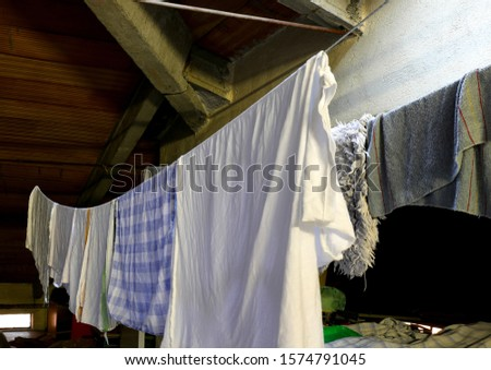 tatters and rags on the washing lines inside an wide attic #1574791045