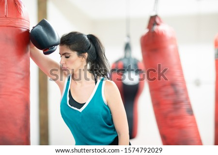 Female boxer taking a break, tired after a workout, leaning her elbow on a boxing bag #1574792029