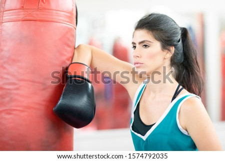 Female boxer leaning on a boxing bag, looking confidently in front of her #1574792035